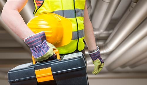 Construction worker carrying toolbox